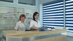 站立在总台的微笑的女性医生在医院 库存图片
