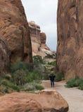 站立在恶魔庭院trailhead的远足者在拱门国家公园在默阿布犹他 库存图片