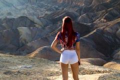 站立在惊人的古老沙漠风景,最热的地方前面的有吸引力的少妇后面视图在世界死亡谷上 免版税库存图片