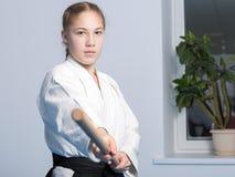 站立在战斗的姿势的黑hakama的一个女孩用木jo棍子 图库摄影