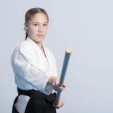 站立在战斗的姿势的黑hakama的一个女孩用木jo棍子 免版税库存图片