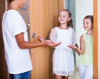 站立在房子入口的三个孩子 免版税库存照片