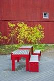 站立在房子前面的表和长凳 免版税库存照片