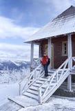 站立在房子旁边的妇女在一个多山区域 免版税库存照片