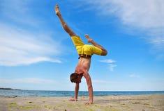 站立在手上的瑜伽人 免版税库存照片