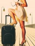 站立在手提箱的妇女一条腿,夏令时 库存照片