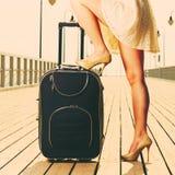 站立在手提箱的妇女一条腿,夏令时 免版税库存照片