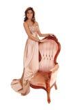 站立在扶手椅子的少妇 免版税库存图片