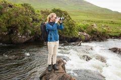 站立在拍照片的小河的一个岩石的白肤金发的妇女 免版税库存照片