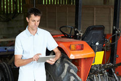 站立在拖拉机旁边的农夫使用数字式片剂 免版税图库摄影