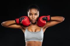 站立在拳击手套的一名美丽的健身妇女的画象 库存图片
