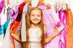 站立在挂衣架之间的逗人喜爱的女孩在购物期间 库存照片