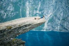 站立在挪威的山的岩石的年轻人 Trolltung 免版税库存照片