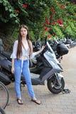 站立在摩托车前面的一个十几岁的女孩 库存图片