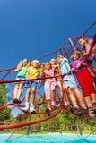 站立在操场网绳索的许多孩子  免版税库存照片