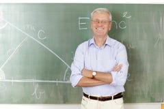 站立在教室的微笑的老师 免版税库存图片