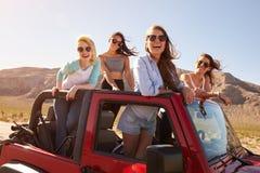 站立在敞篷车汽车的旅行的四个女性朋友 免版税库存图片