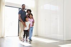 站立在新的家里空的屋子的激动的家庭画象在移动的天 库存图片