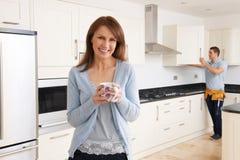 站立在新的豪华适合的厨房里的妇女 图库摄影