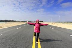 站立在新的路的一条腿的妇女在冬天 免版税库存照片