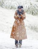 站立在新鲜的落的白色雪的愉快的妇女 库存照片