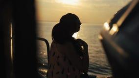 站立在旅游船上和享受日落的一个美丽的女孩的后方特写镜头 股票视频