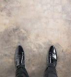 站立在旅途初的商人注视着下来他的脚 免版税库存图片