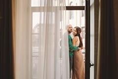 站立在旅馆客房的阳台的年轻夫妇 库存照片