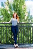 站立在旅馆的阳台的红发女孩 免版税库存图片