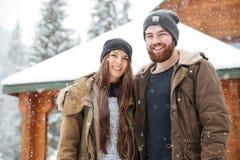 站立在日志cabine前面的夫妇在冬天 免版税库存照片