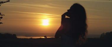 站立在日落的女孩 免版税库存图片