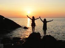 站立在日落的岩石海边的两个剪影女孩 库存照片