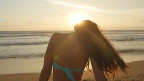 站立在日落的海附近的比基尼泳装的美丽的少妇 有摆在海洋的长的头发的可爱的性感的女孩 股票视频