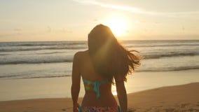 站立在日落的海附近的比基尼泳装的美丽的少妇 有摆在海洋的长的头发的可爱的性感的女孩 库存图片