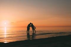 站立在日落背景的水亲吻的一对成人夫妇的剪影 免版税库存图片