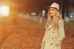 站立在时兴的米黄帽子的美丽的端庄的妇女在一个公园在秋天 copyspace,阳光 免版税库存照片