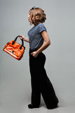 站立在时髦有橙色袋子的衣裳皮靴的年轻时尚女孩 库存照片