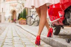 站立在时髦的红色moto滑行车旁边的高跟鞋的妇女 免版税库存照片