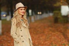 站立在时兴的米黄帽子的美丽的端庄的妇女在一个公园在秋天 免版税库存照片