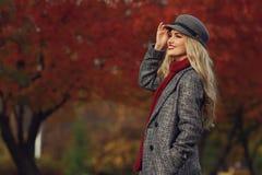 站立在时兴的米黄帽子的美丽的端庄的妇女在一个公园在秋天 Copyspace 图库摄影