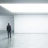 站立在明亮的办公室的商人 免版税图库摄影