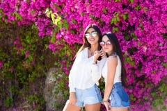 站立在明亮的桃红色花五颜六色的自然本底的美丽的愉快的时尚年轻女人  免版税库存照片