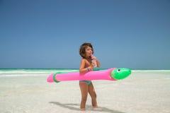 站立在明亮的晴朗的沙子海滩的小女孩 免版税库存照片