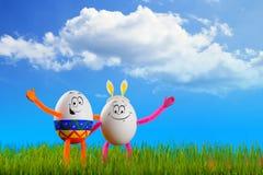 站立在春天草的两个滑稽的复活节彩蛋 免版税库存图片