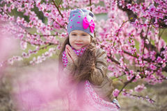 站立在春天年轻桃树的领域的逗人喜爱的美丽的时髦的加工好的白肤金发的女孩与桃红色花的 女孩微笑 库存照片