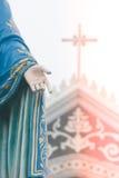 站立在是公共场所的天主教主教管区前面的保佑的圣母玛丽亚雕象的手 库存照片
