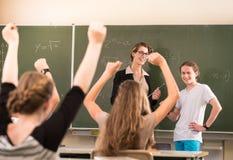 站立在是准备充分的学生前面的数学老师 库存照片