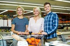 站立在显示附近的愉快的家庭用冷冻食品 免版税库存照片