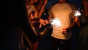 站立在更轻的火附近的朋友在夜期间在他们的手上集会在海边点燃孟加拉闪烁发光物光 股票录像