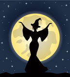 站立在月亮的背景的美丽的巫婆 库存图片